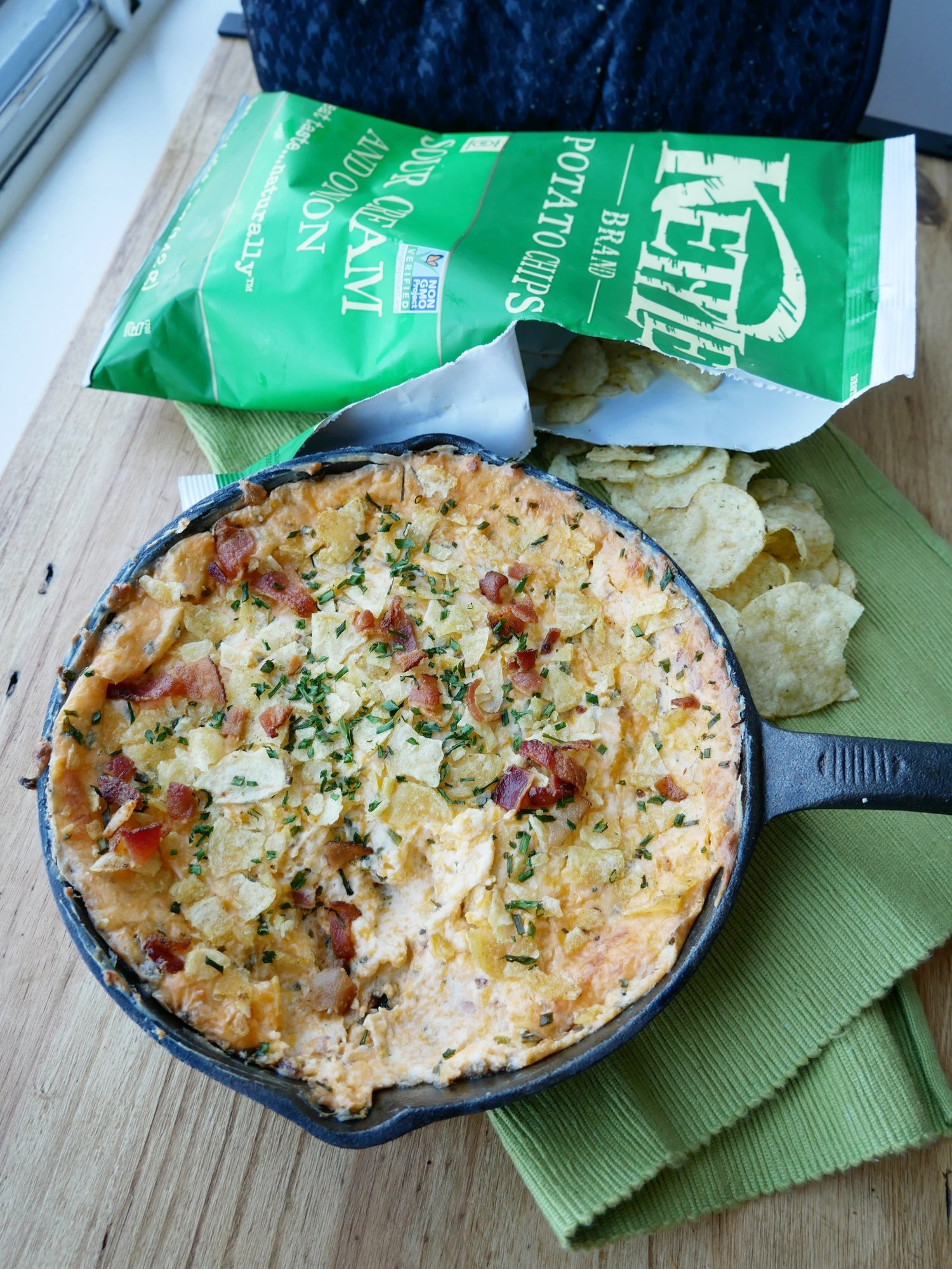 a skillet of sour cream and onion bacon cheesy chive dip topped with chips and bacon