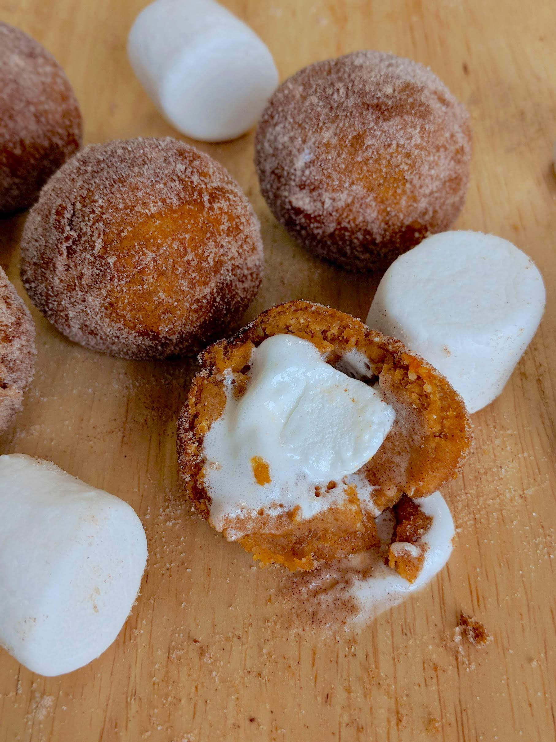 a close up of a sweet potato donut hole stuffed with a marshmallow