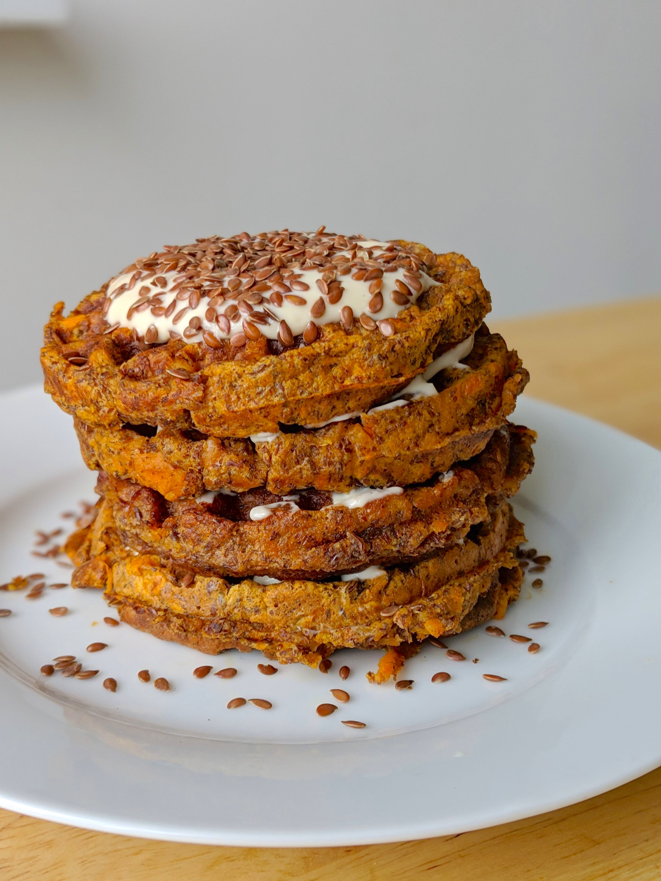 a stack of sweet potato carrot cake waffles with frosting in between and on top, and crunchy flax seeds