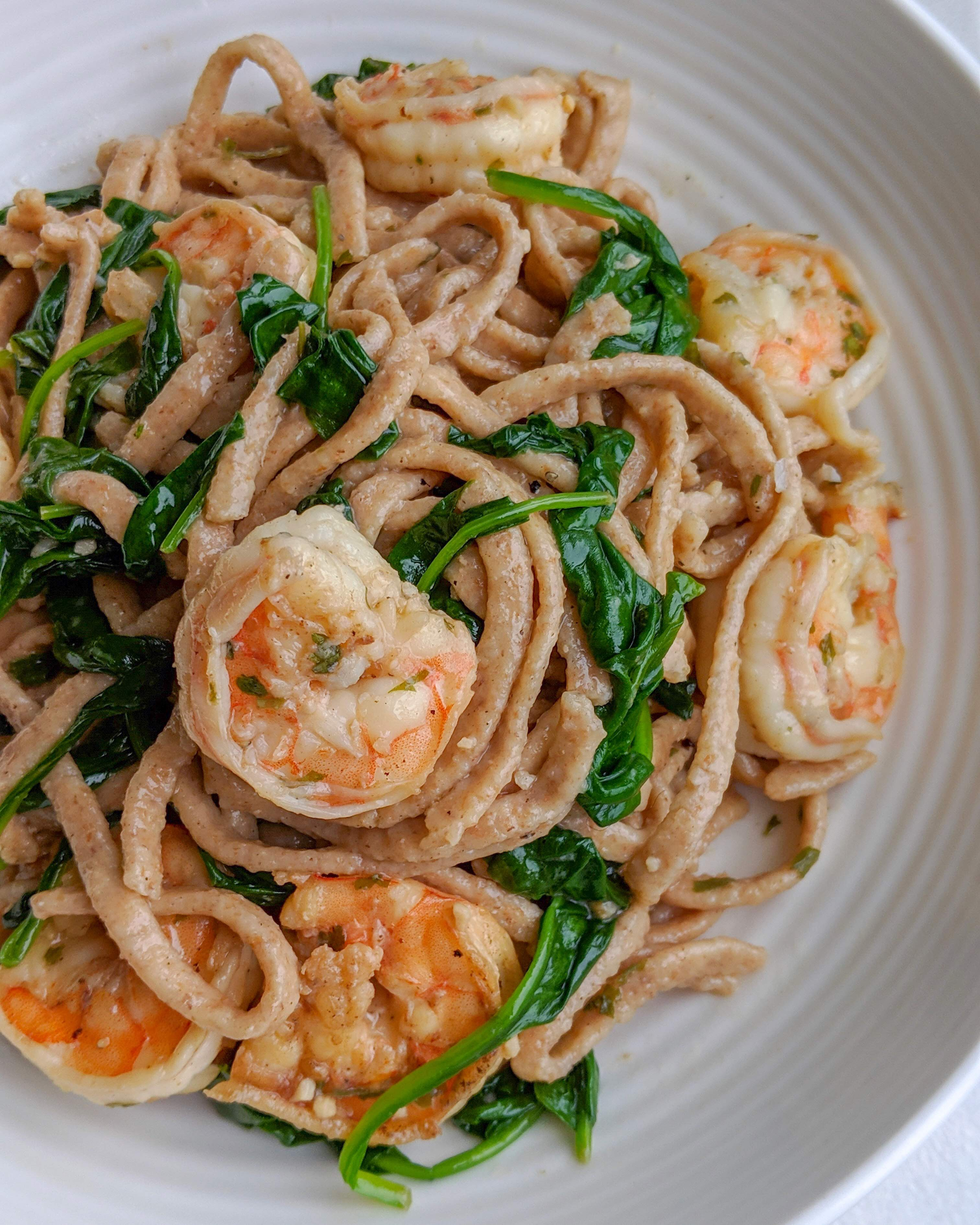 A plate of farro pasta with a butter and garlic white wine sauce, tossed with seared shrimp and spinach