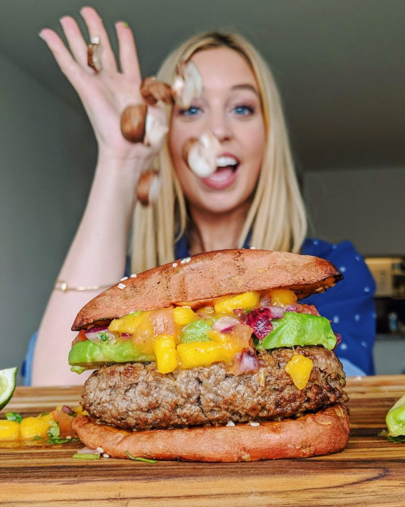 Blonde girl throwing mushrooms onto a caribbean burger with mango salsa and avocado