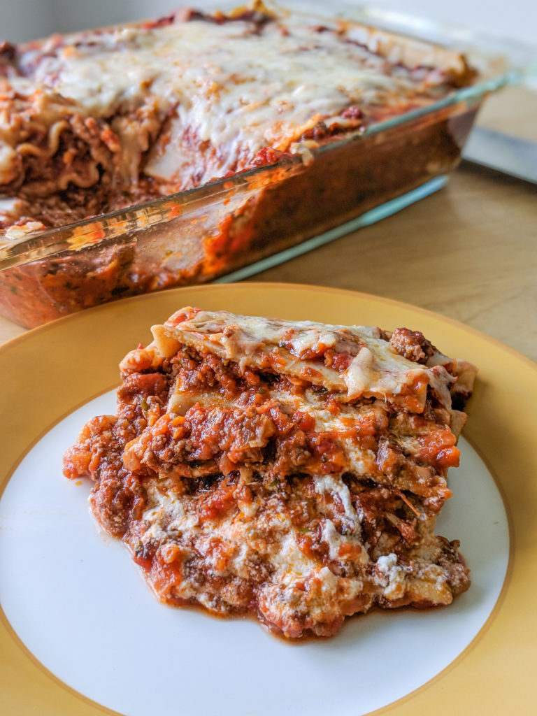 One slice of meat lasagna with layers of cheese, pasta and beef