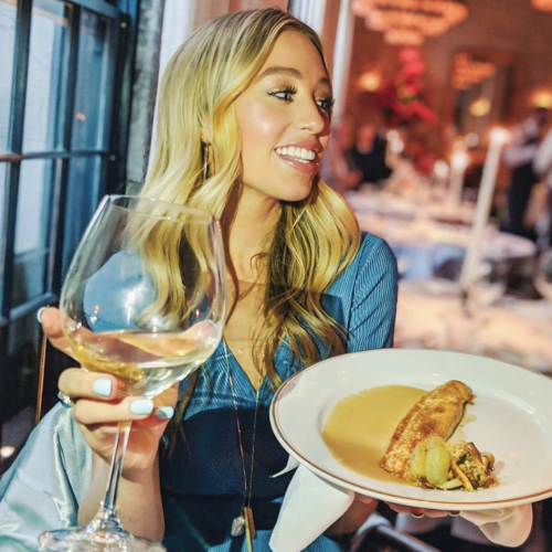 Blonde woman enjoying a glass of white wine and a plate of dover sole in NYC restaurant Le Coucou
