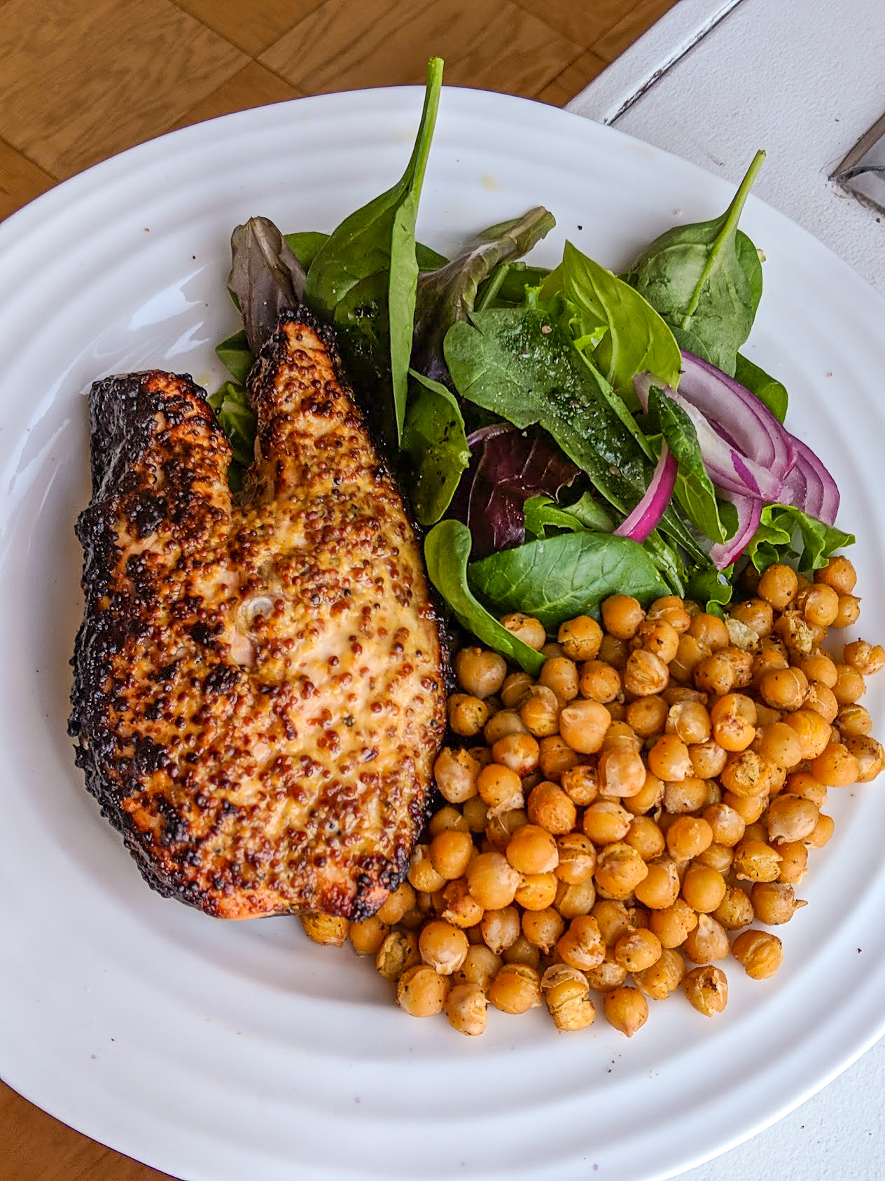 A full plate featuring a savory dijon-mustard salmon steak with a side of roasted chickpeas and a spinach salad.