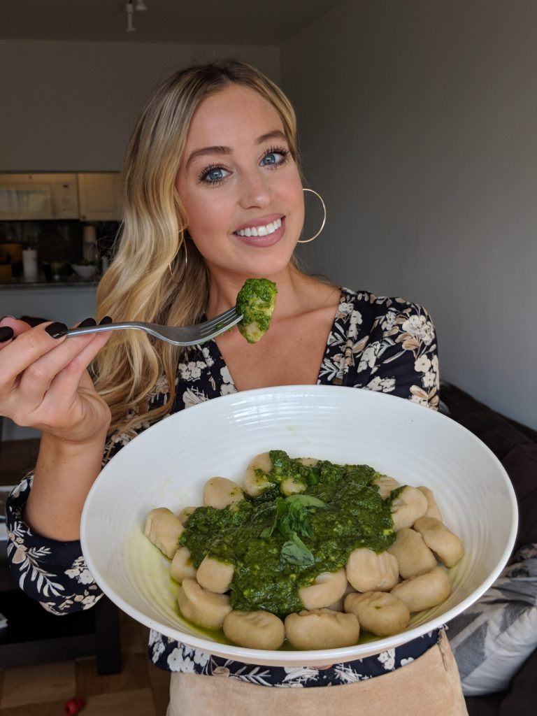Woman holding a bowl full of cauliflower gnocchi with spinach avocado pesto dining with skyler