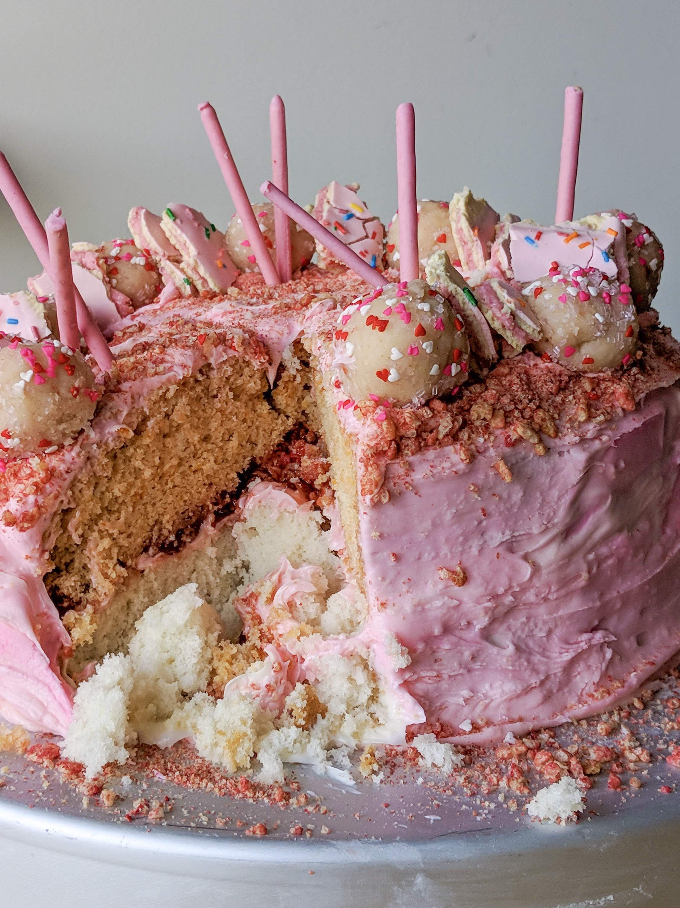 layered strawberry and vanilla cake with strawberry jam and strawberry crispy cereal, strawberry pop-tarts, cake balls and pocky sticks