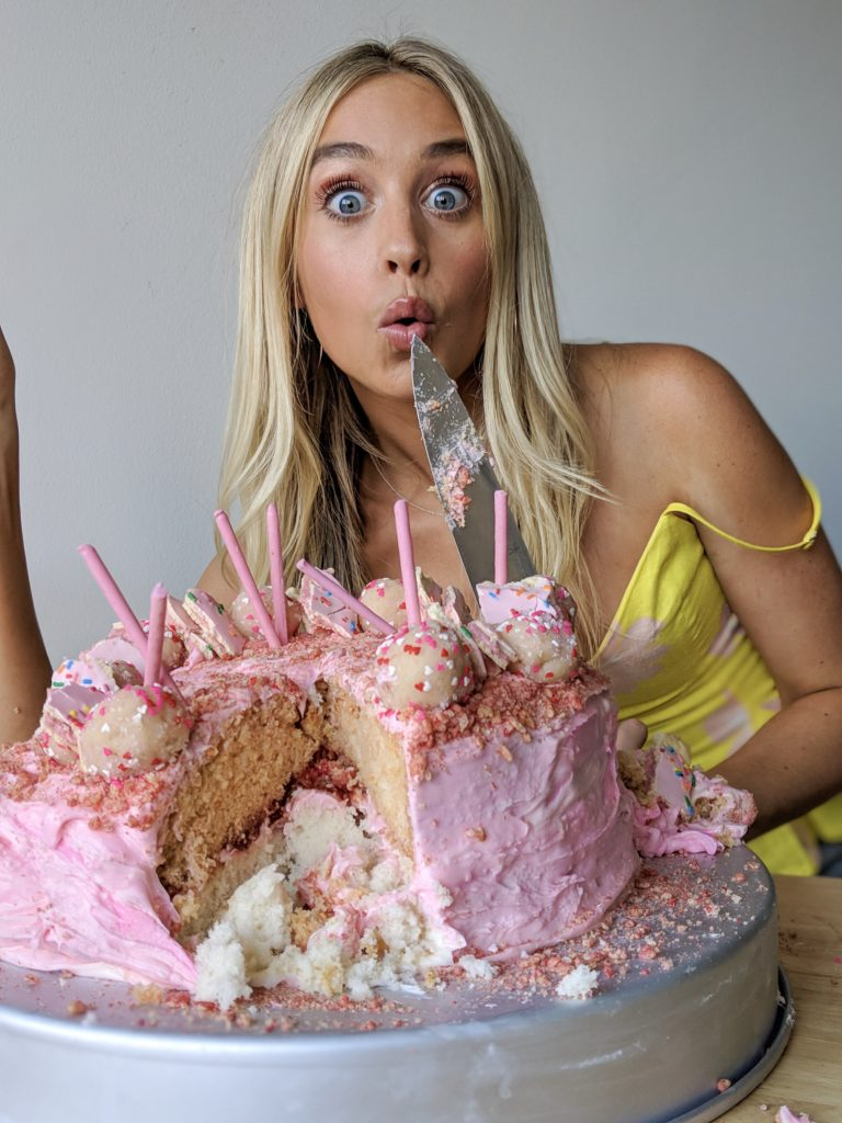 Skyler Bouchard with a pink cake with cake truffles on top