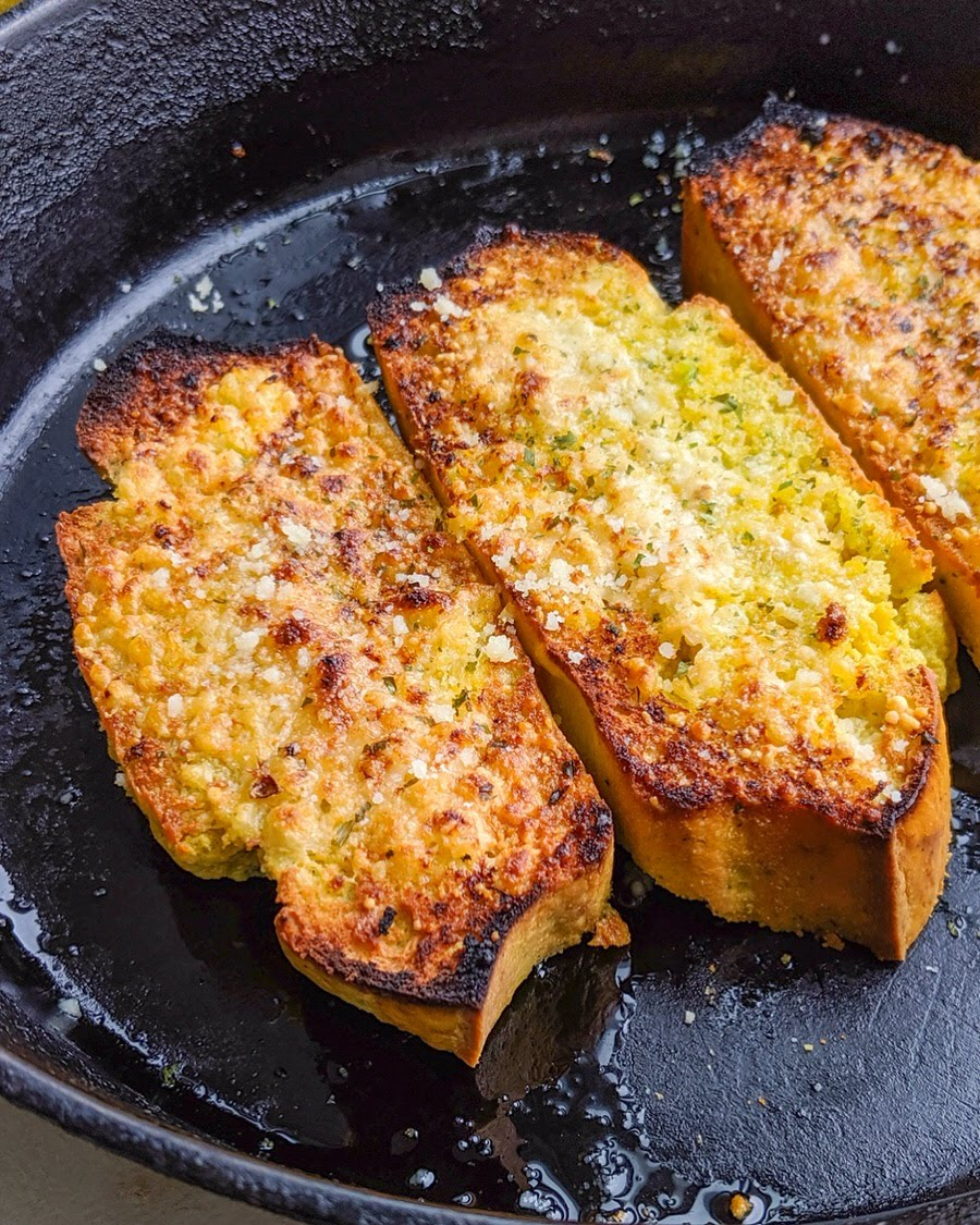 Skillet full of two pieces of crispy grain-free garlic Texas toast