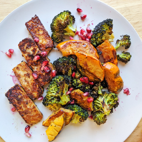 Plate of seared golden brown pumpkin spice halloumi with broccoli and acorn squash and pomegranate