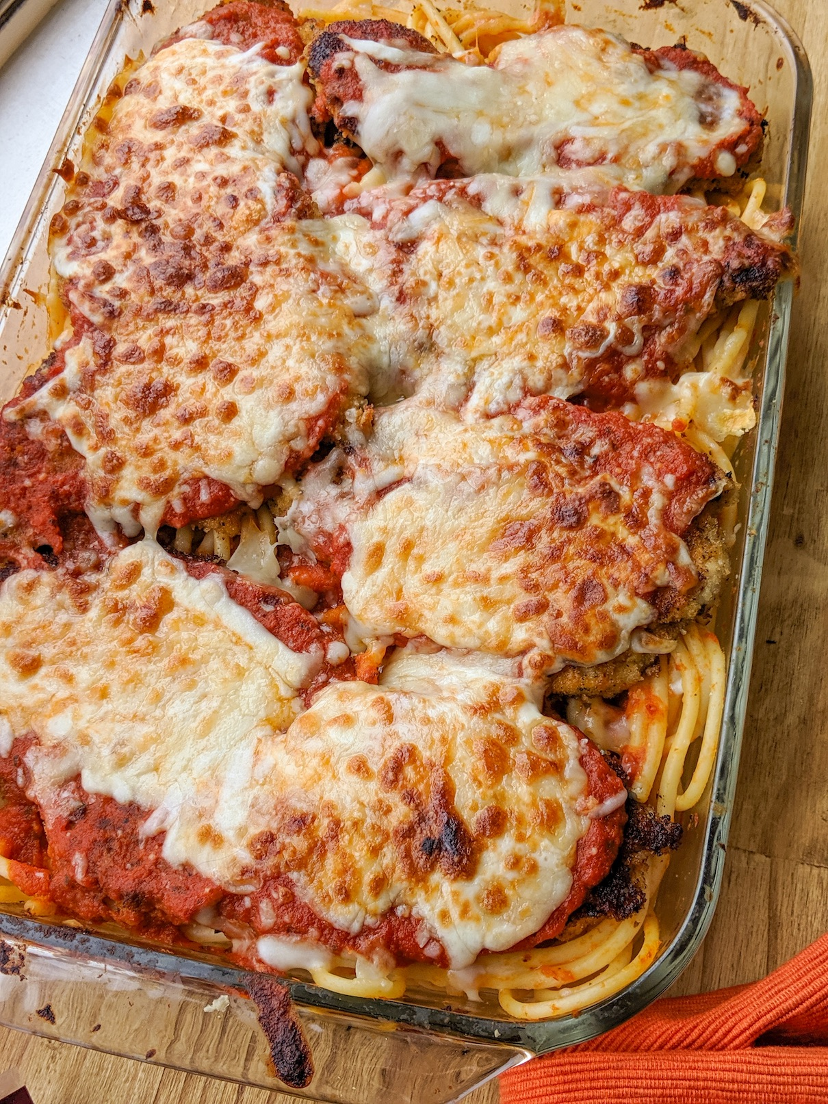 a platter of bucatini covered in cheesy turkey cutlet parmesan
