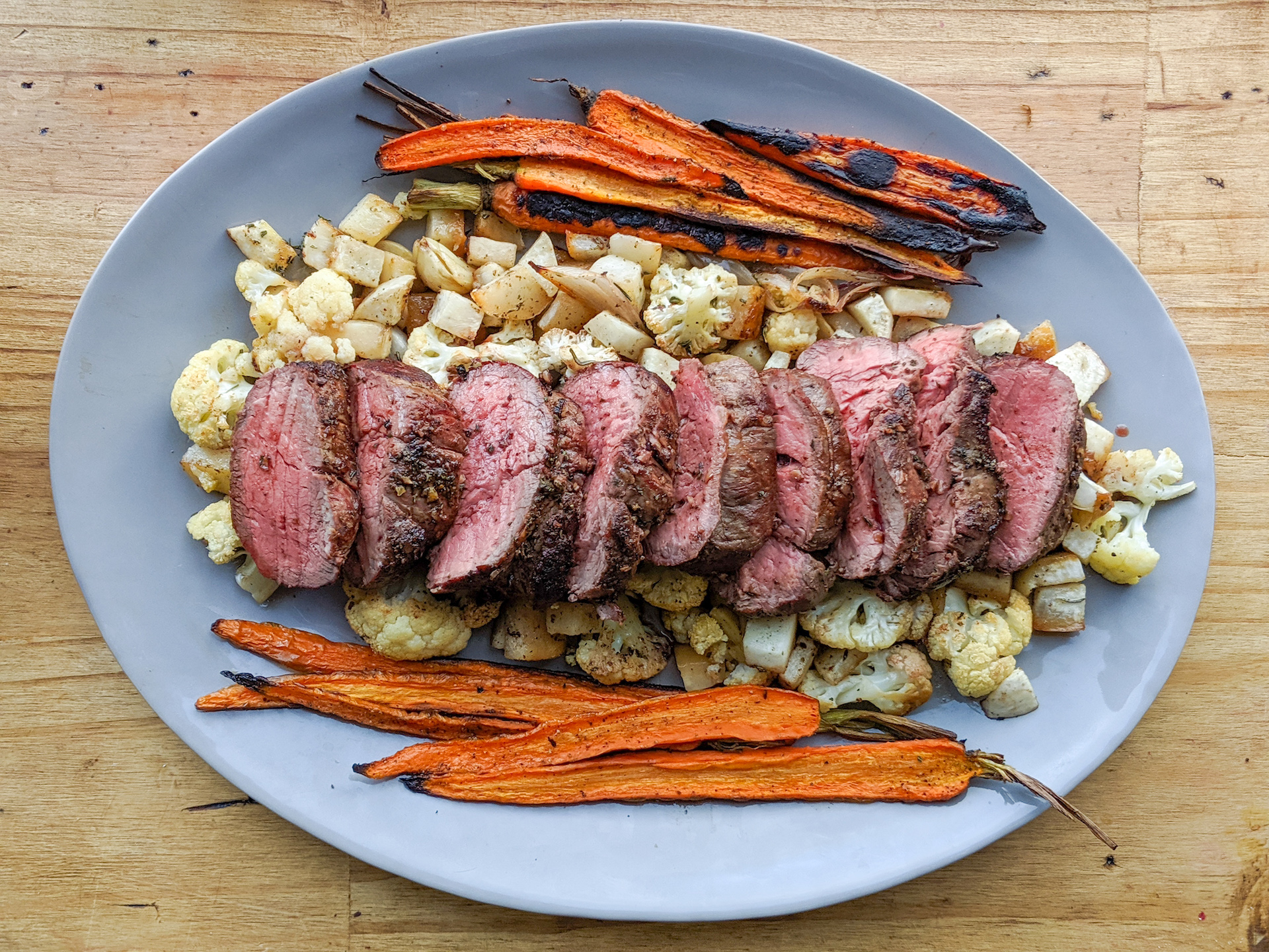 Platter of roast beef tenderloin with carrots, turnips and cauliflower