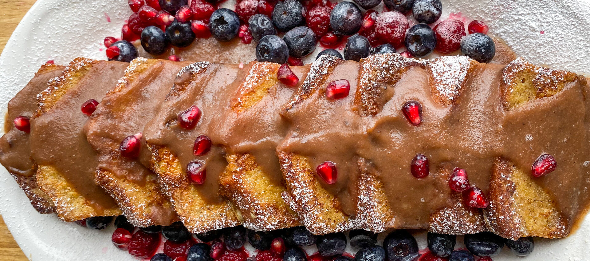 a beautiful platter of golden brown pound cake french toast with an assortment of berries and chestnut syrup drizzled on top
