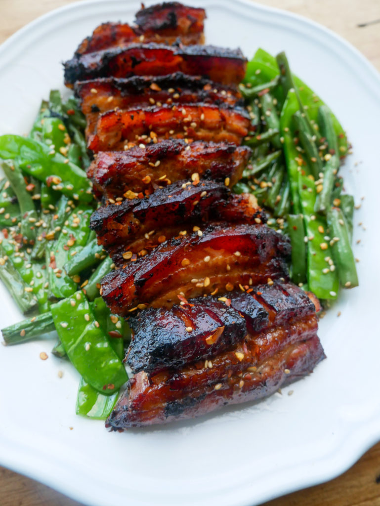 a plate of crispy pork belly with green beans, snap peas and sesame seeds