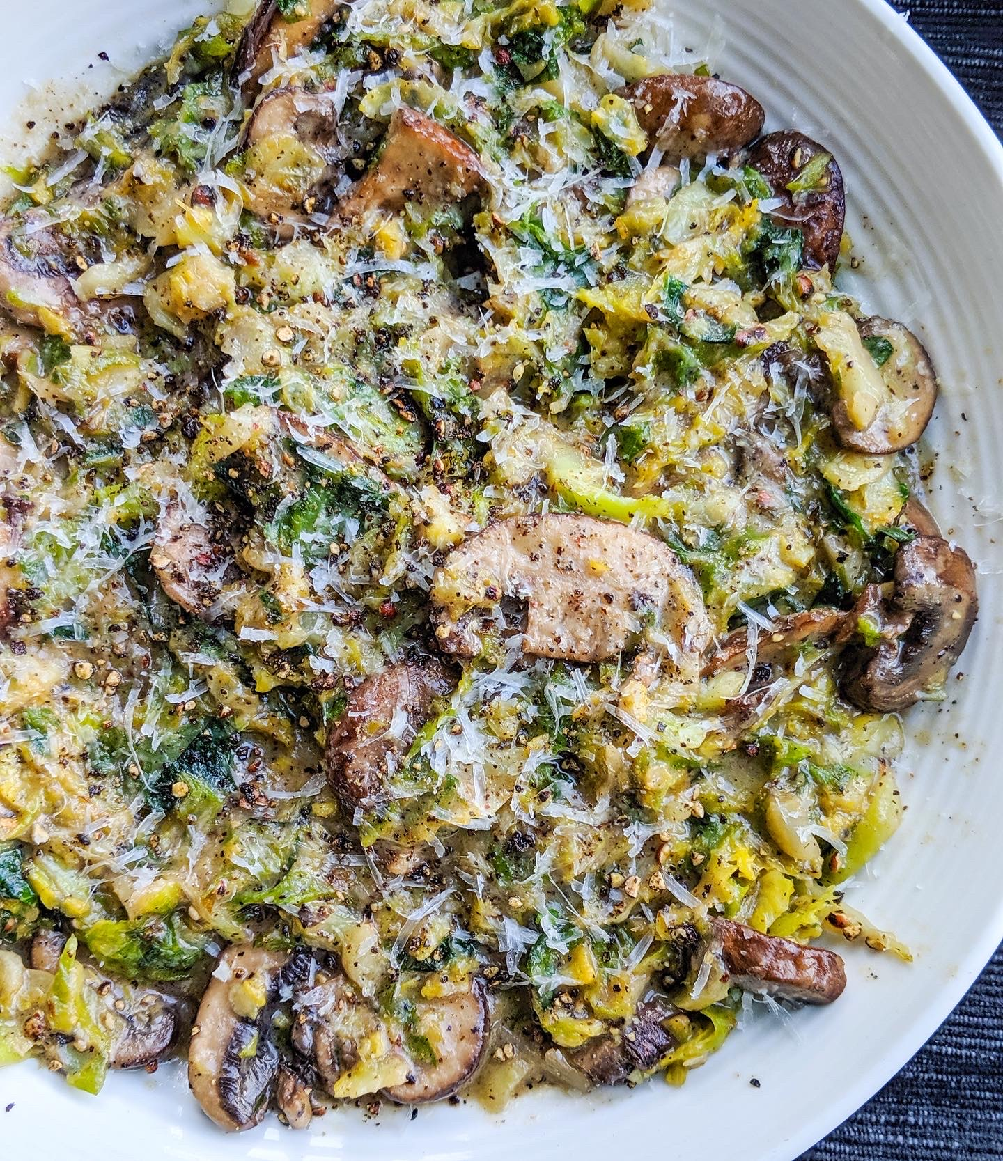 a large bowl of Cacio e Pepe shaved brussels sprouts and mushrooms