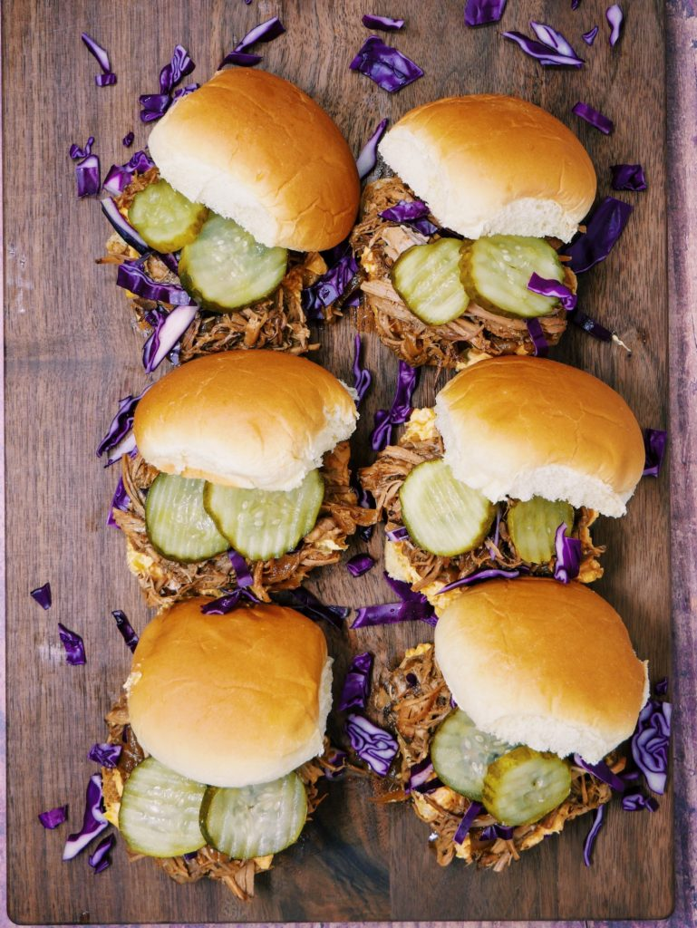 a plate of Slow Cooker Pulled Pork Sriracha Pimento Sliders with pickles and red cabbage