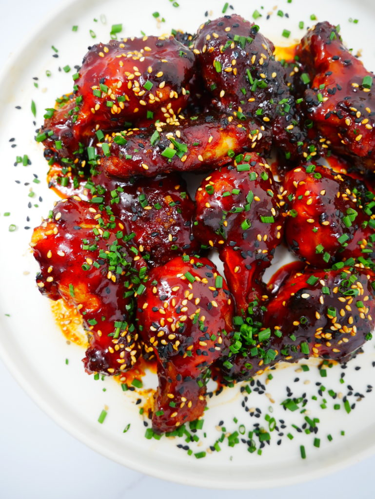 a plate of honey gochujang baked chicken wings with sesame seeds and chives