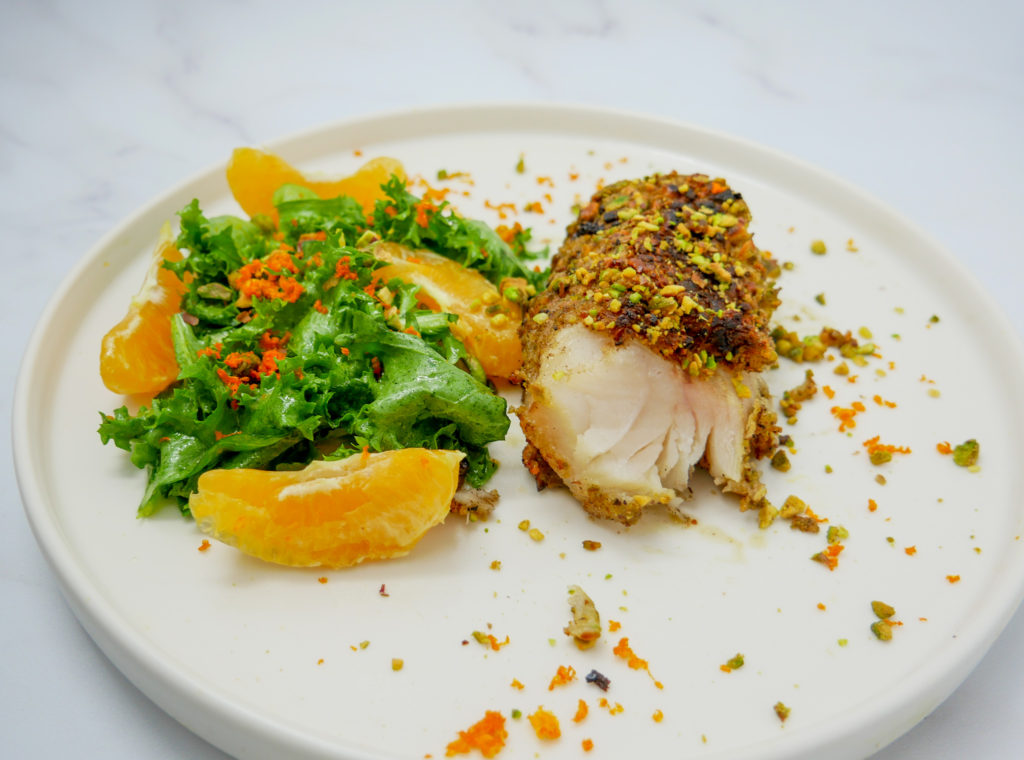 a bright plate of pistachio crusted cod with an escarole salad and orange lime vinaigrette