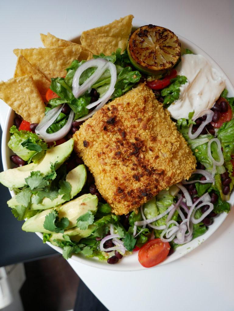 a plate of taco salad with tortilla chip crusted mahi mahi