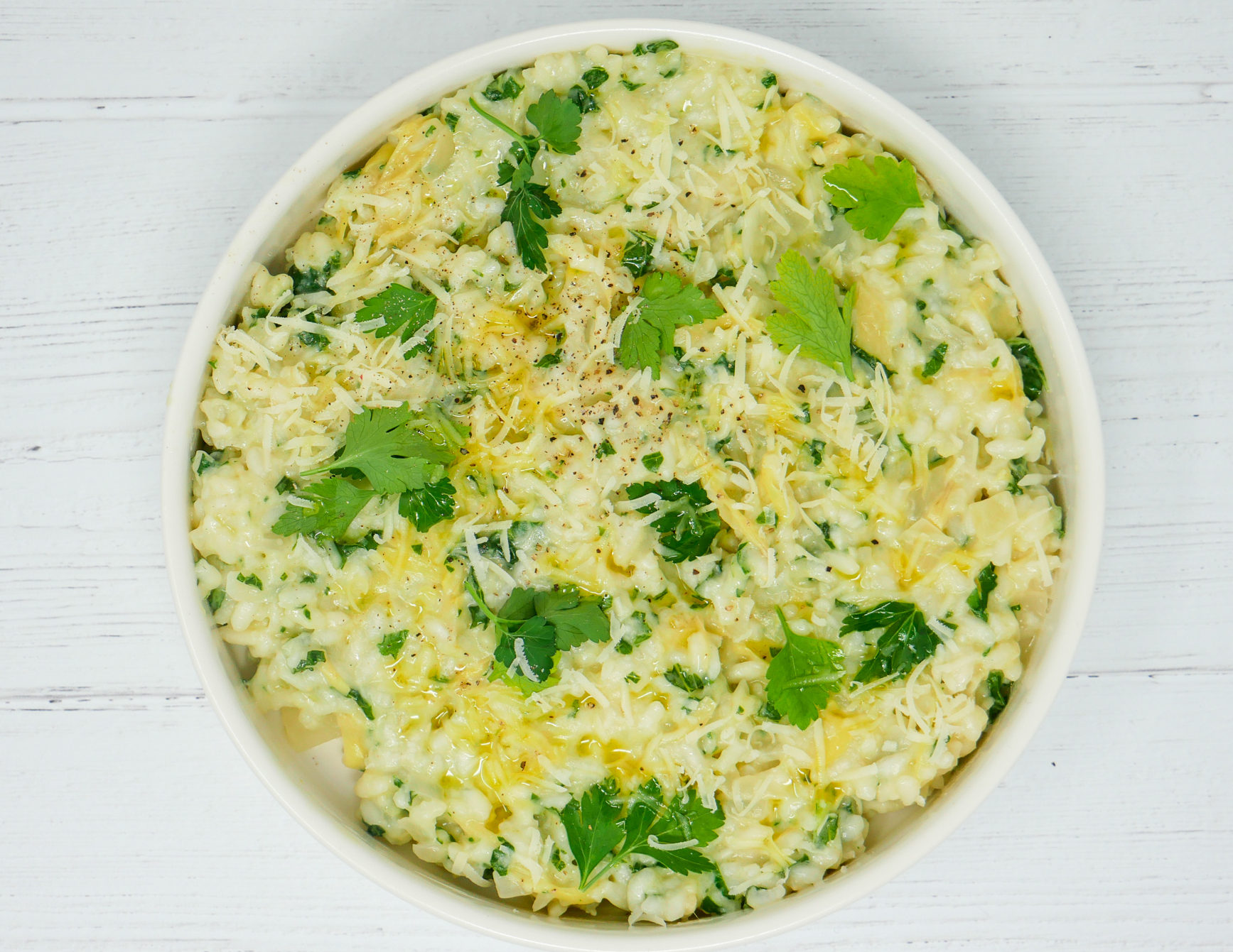 a bowl of creamy artichoke kale risotto with pecorino and fresh parsley
