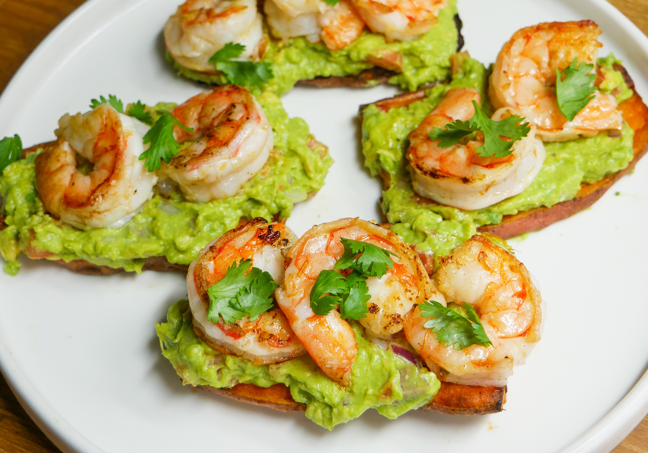 a plate of shrimp guacamole sweet potato toasts