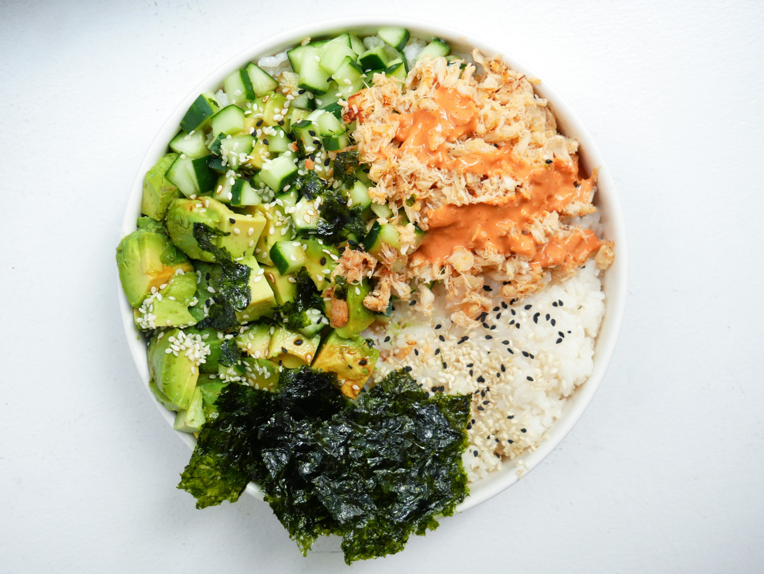 California roll poke bowl with avocado, cucumber, spicy mayo and seaweed