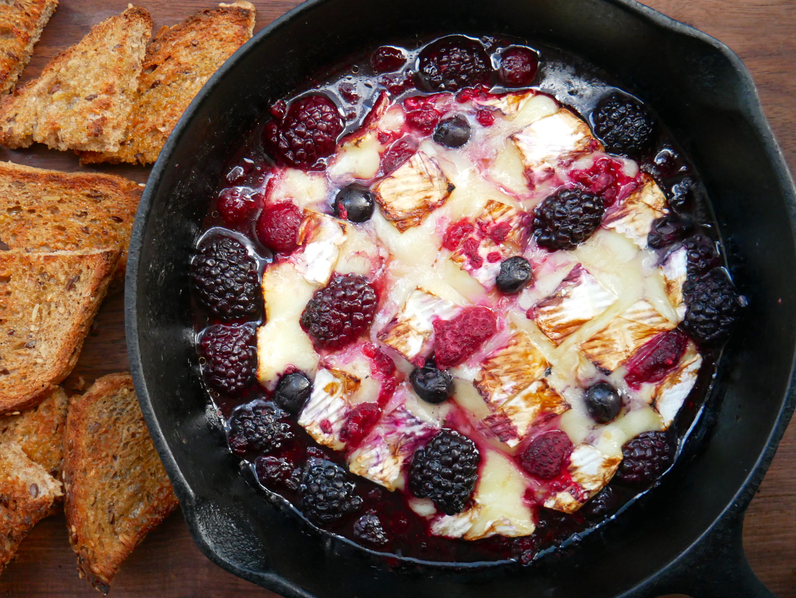 balsamic berry baked brie in a skillet with toast
