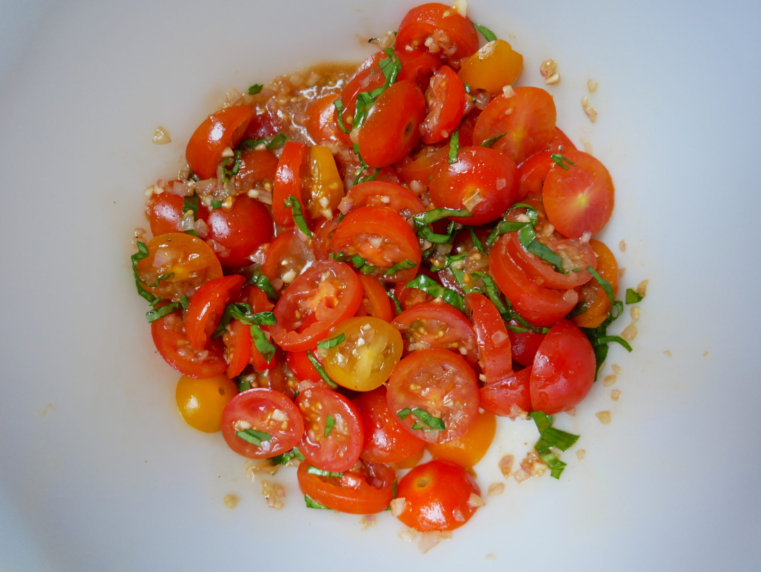 a bowl of tomatoes, basil, garlic and shallots
