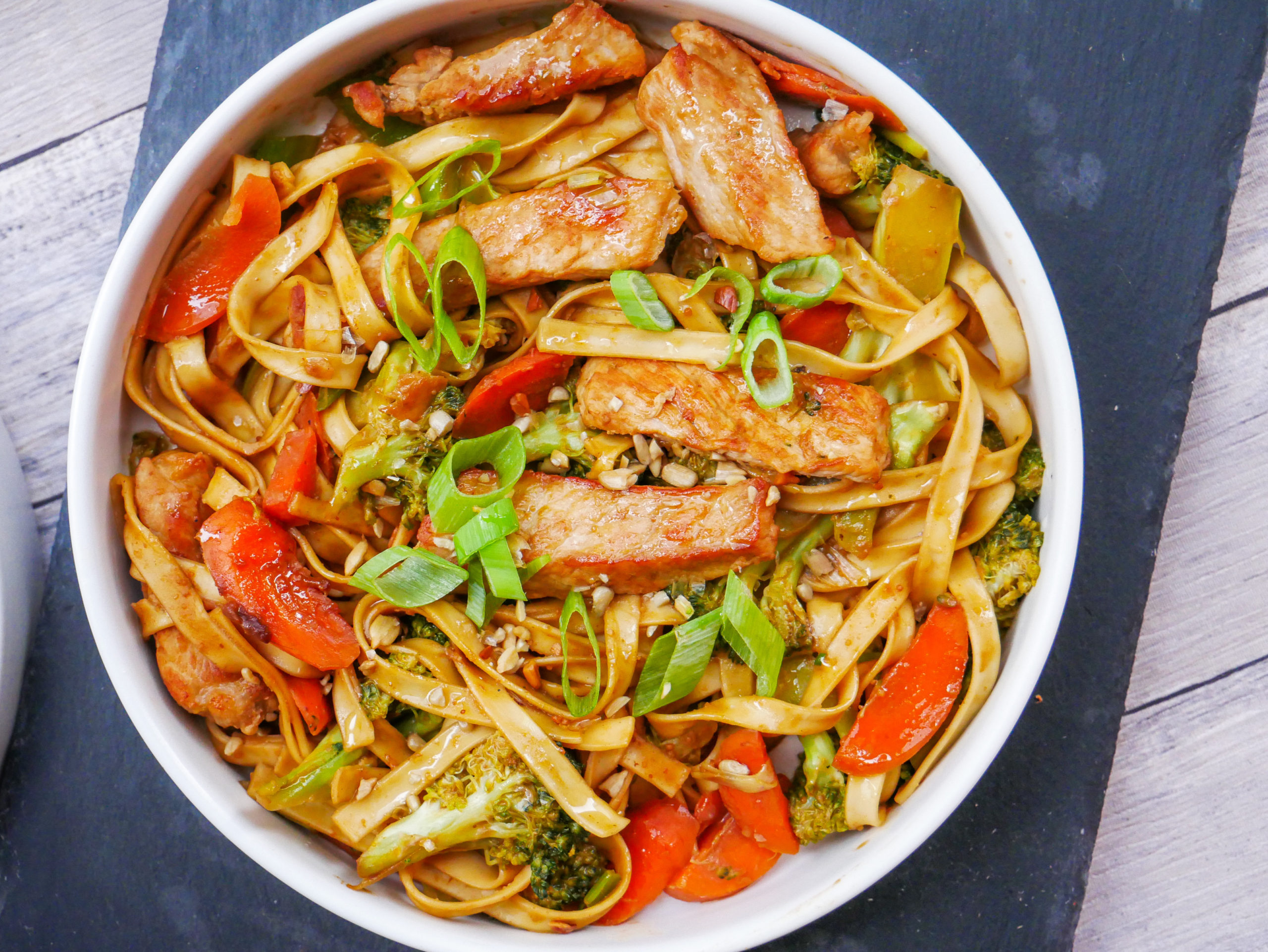 pork and noodle stir fry in a savory peanut sauce