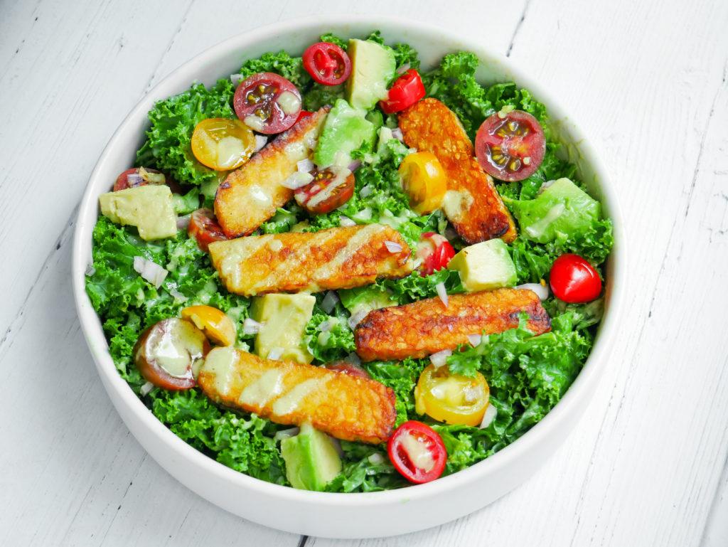 vegan kale caesar with tempeh, avocado, cherry tomatoes, shallots
