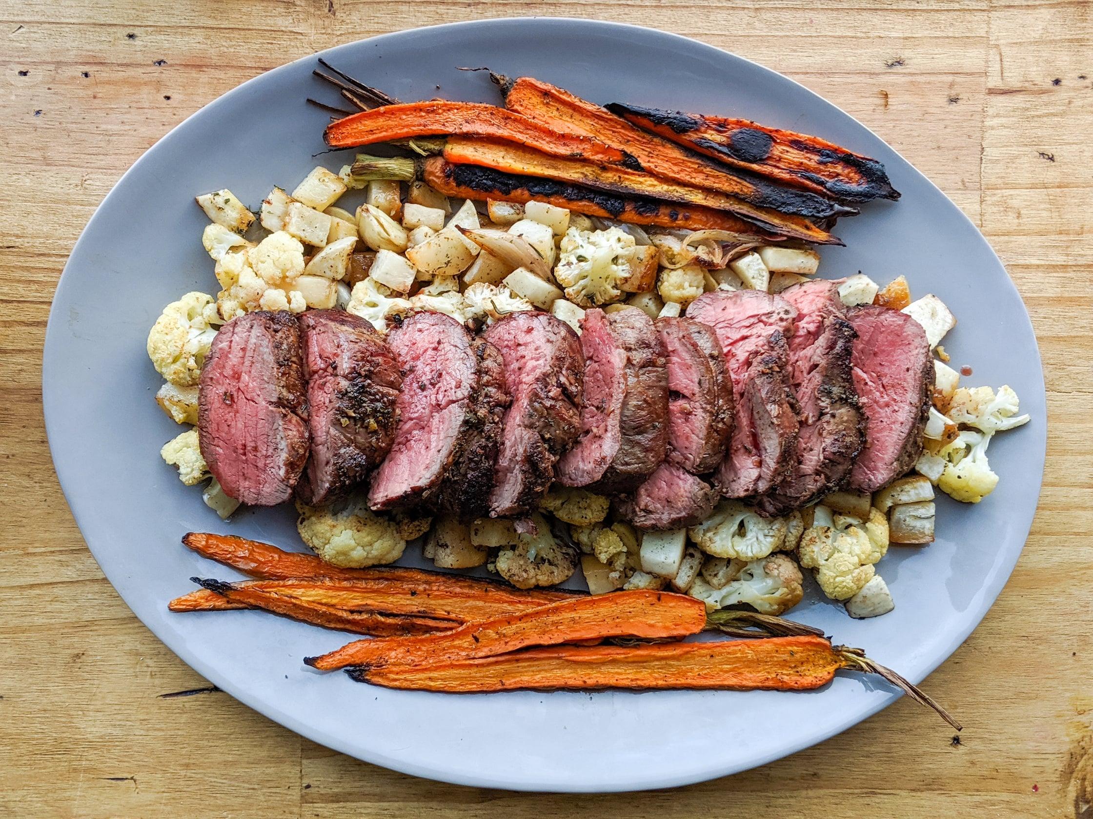 a platter of beef tenderloin and roasted veggies