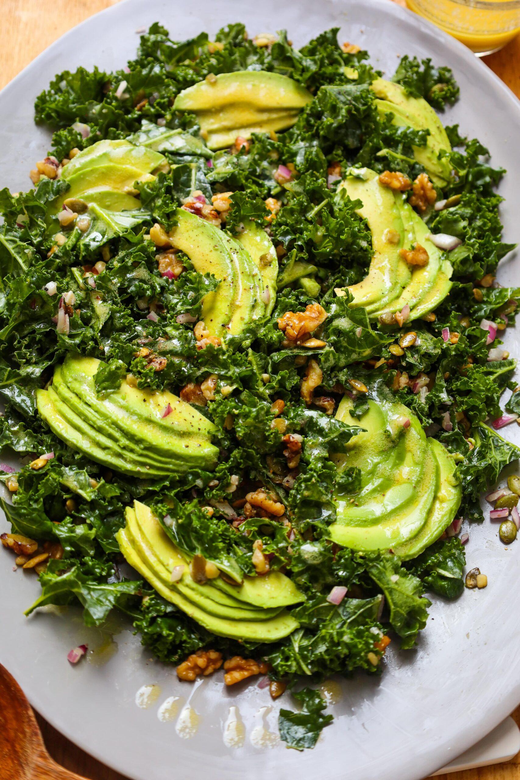 kale salad with walnuts, pumpkin seeds avocado and dijon vinaigrette