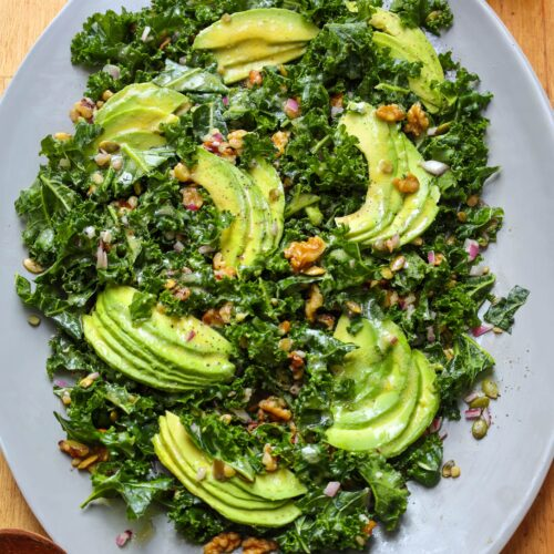 kale salad with walnuts, pumpkin seeds avocado and dijon vinaigrette